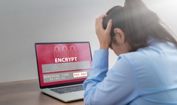Stressed business woman with computer screen showing personal files encrypted text, Ransomware malware attack. Business computer Hacked. files encrypted.