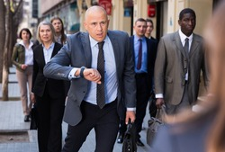 Stressed businessman is late for meeting, checking time hastily on his watch and running on city street..