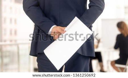 Stressed businessman job applicant in suit holding cv paper behind back preparing for speech interview feeling nervous, afraid of public speaking and fear of failure concept, rear close up view