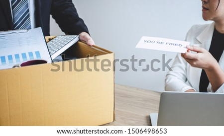 Stressed businessman receive fired letter from employer and packing belongings and files into brown cardboard box, changing and resigning from work concept.