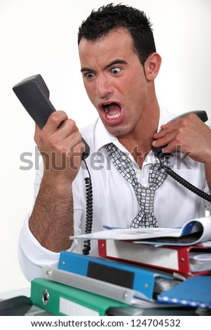 Stressed businessman screaming at a phone
