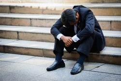 Stressed businessman sitting at stairway outdoor.Bankrupt businessman sitting outdoor.