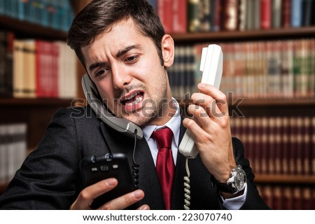 Stressed businessman talking on many phones at once Сток-фото ©
