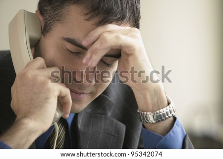 Stressed businessman talking on phone