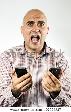 Stressed businessman using two smartphone devices at the same time, looking really stressed and hassled