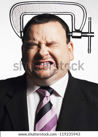 Stressed businessman with clamp on head over white background - stock photo