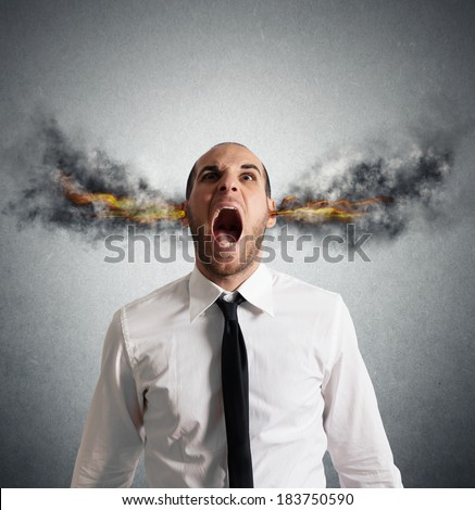 Stressed businessman with smoke and flame in head - stock photo