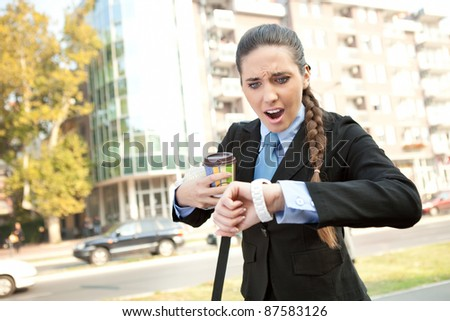 stressed businesswoman checking the time, outdoor
