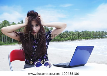 Stressed businesswoman with laptop scratching her hair on the beach