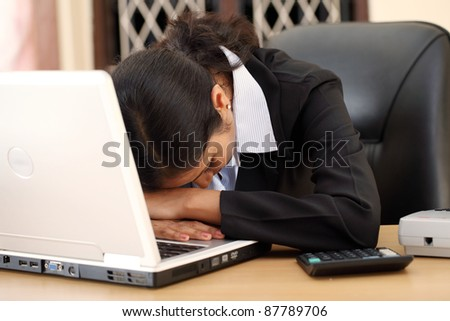 Stressed businesswoman working on laptop