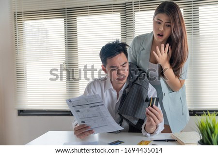 Stressed couple young family husband and wife looking so many expenses bills such as electricity bill,water bill,internet bill,cell phone bill and credit card bill in his hand no money to pay debt Photo stock ©