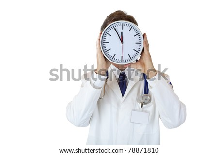 Stressed doctor with clock in front of face as sign of time pressure.Isolated on white background.