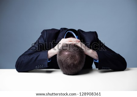 Stressed employee with head on a table.