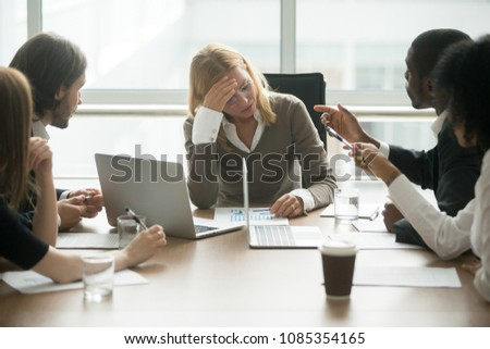 Stressed exhausted businesswoman tired of disrespect or discrimination at multiracial meeting, disappointed depressed woman boss feeling sad about colleagues criticizing at diverse group briefing