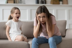 Stressed exhausted mother looking at camera feeling desperate about screaming stubborn kid daughter tantrum, upset annoyed mom tired of naughty difficult child girl misbehave yelling for attention