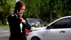 Stressed female driver talking phone car collision scene, auto damage, insurance