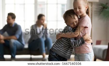 Stressed little girl embracing smaller brother, overcoming parents argue divorce together. Unhappy frustrated kids siblings suffering from family quarrels, misunderstanding of father and mother. Stock photo ©