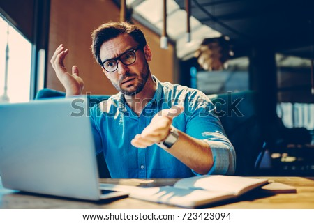 Stressed male entrepreneur disappointed with bad wifi connection in coffee shop while doing remote job.Angry businessman shocked with company web site failure browsing page on laptop computer