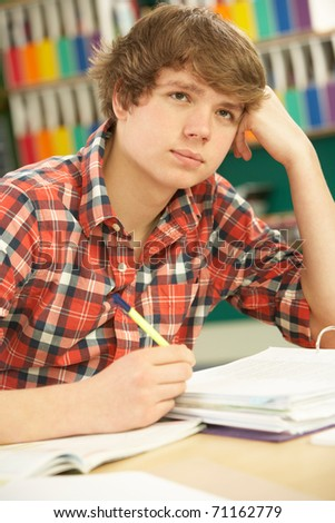 stock photo : Stressed Male Teenage Student Studying In Classroom