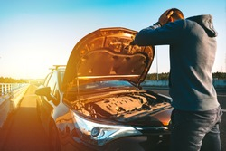 Stressed man having trouble with his broken car on the highway roadside at sunset. Man looking under the car hood. Car breaks down on the autobahn. Roadside assistance concept.