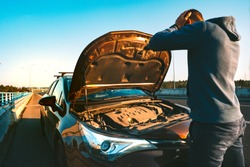 Stressed man having trouble with his broken car on the highway roadside. Man looking under the car hood. Car breaks down on the autobahn. Roadside assistance concept.
