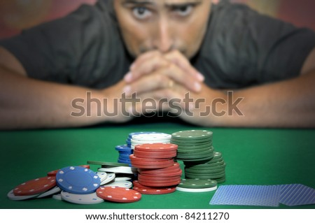Stressed man in a poker table gambling