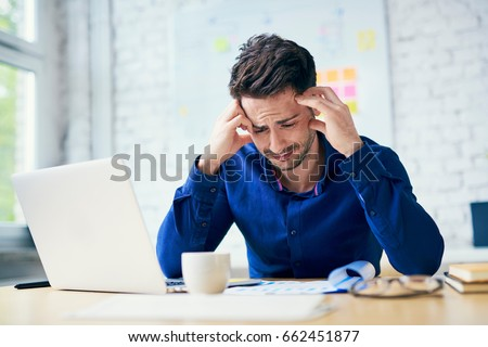 Stressed man in office looking on documents