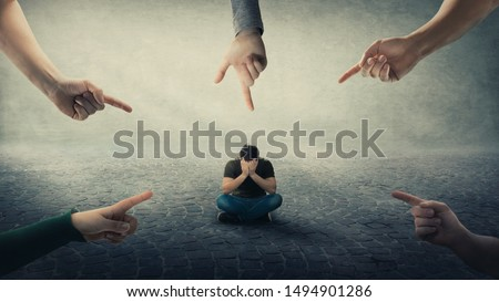 Stressed man, under pressure, sitting on floor cover face feel discomfort as a lot of hands pointing forefingers to him blaming as guilty. Human depression, social anxiety, victim of mental distress.