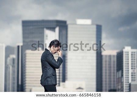 Stressed man walking in the city with storm clouds rolling in.