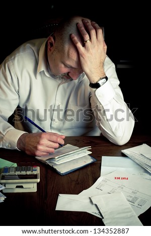 Stressed man with checkbook struggling while working on household finances