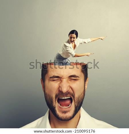 stressed man with open head. young screaming woman standing into the head, looking at the man and showing the direction. photo over grey background