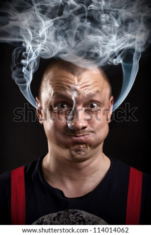 Stressed man with waving smoke from ears
