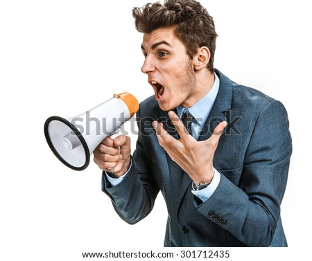 Stressed man yelling through a megaphone  / photos of young businessman wearing  a suit and tie over white background Сток-фото ©