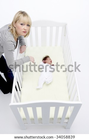 Stressed Mother Looking At Baby In Cot