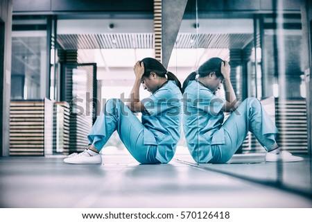 Stressed nurse sitting in hospital corridor