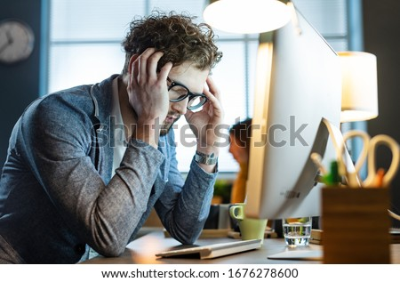 Stressed office worker sitting at desk and working with his computer, he is tired and having a headache