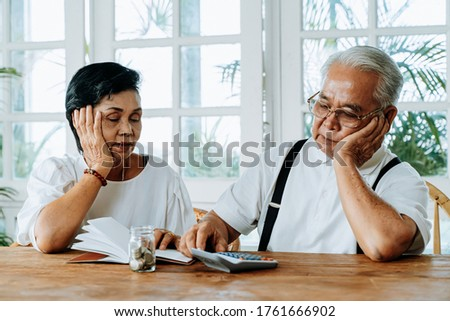 Stressed old Asian senior couple worried about unpaid bank bills. Serious elderly family using calculator to count for loan payment and having money problem Stock photo ©