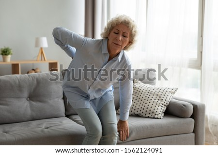 Stressed old senior adult lady touching back feel lower lumbar ache getting up from sofa at home, upset elderly grandma suffer from backache health problem, osteoarthritis disease, backpain concept