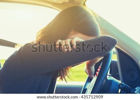 stressed or tired girl in car lying on steering wheel