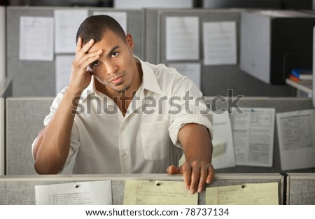 Stressed-out Latino office worker with hand on his head