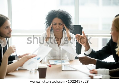 Stressed overwhelmed african businesswoman feels tired at corporate meeting, exhausted black female boss suffering from headache touching temples at team briefing, stress at work or migraine concept Stock photo ©