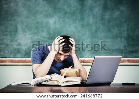 Stressed overworked man studying in front of notebook holding a paper in hand thinking to start from the beginning again isolated on a blackboard background.Facial expression.Idea.