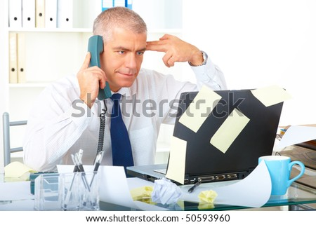 Stressed overworked mature businessman sitting at desk with phone and looking at laptop with many notes stickers