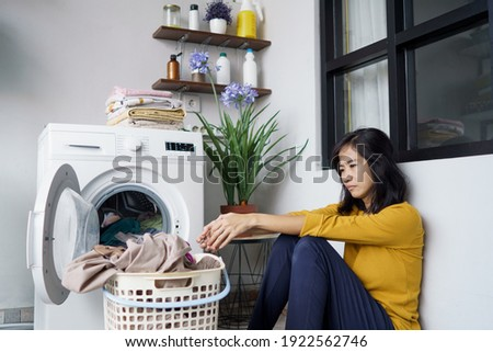 stressed pretty asian housewife doing some laundry at home Stock photo ©