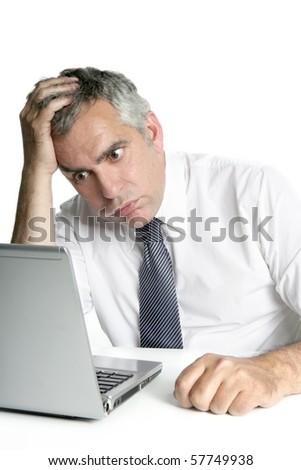 stressed senior businessman gesture working laptop computer white desk