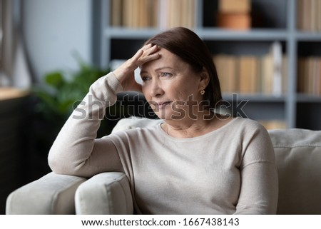 Stressed senior retired woman touching forehead, looking away, feeling doubtful about decision. Unhappy thoughtful middle aged lady sitting on couch, worrying about personal problems alone at home.