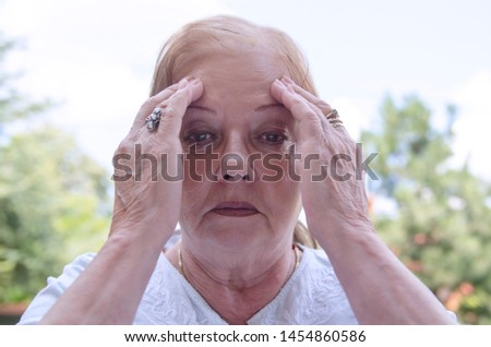Stressed senior woman head shot,holding hands on head having memory loss.Dementia health problem of old people
