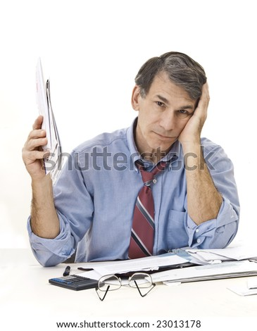 Stressed, tired, overworked businessman doing paperwork, worrying about the economy, his credit, etc.