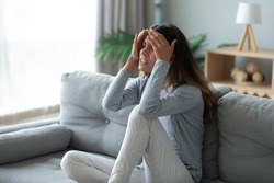 Stressed unhappy woman touching forehead, suffering from strong headache or chronic migraine, sick unhealthy girl feeling pain in head, sitting on couch at home alone, health problem