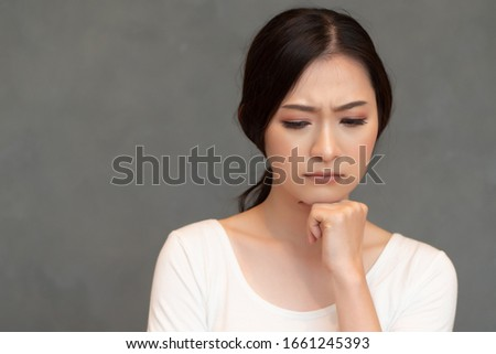 stressed upset thoughtful asian woman thinking, planning about problem; portrait of asian woman looking down with worry, thinking, finding good idea or plan; adult Chinese, east asian woman model Foto stock ©